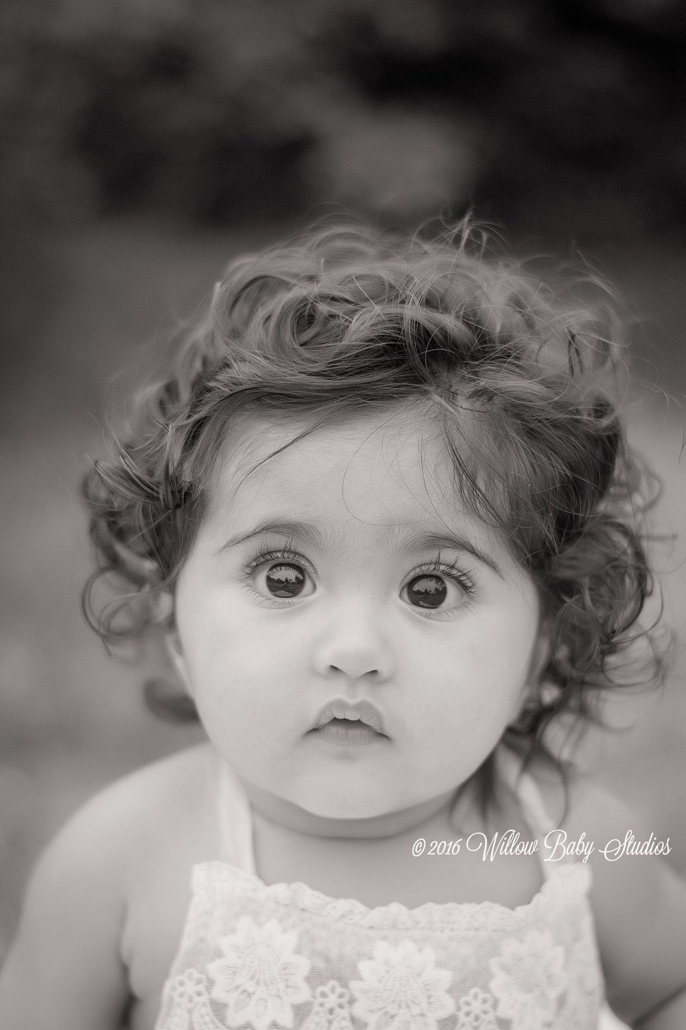 black and white photo of 6 month old staring intently at the camera