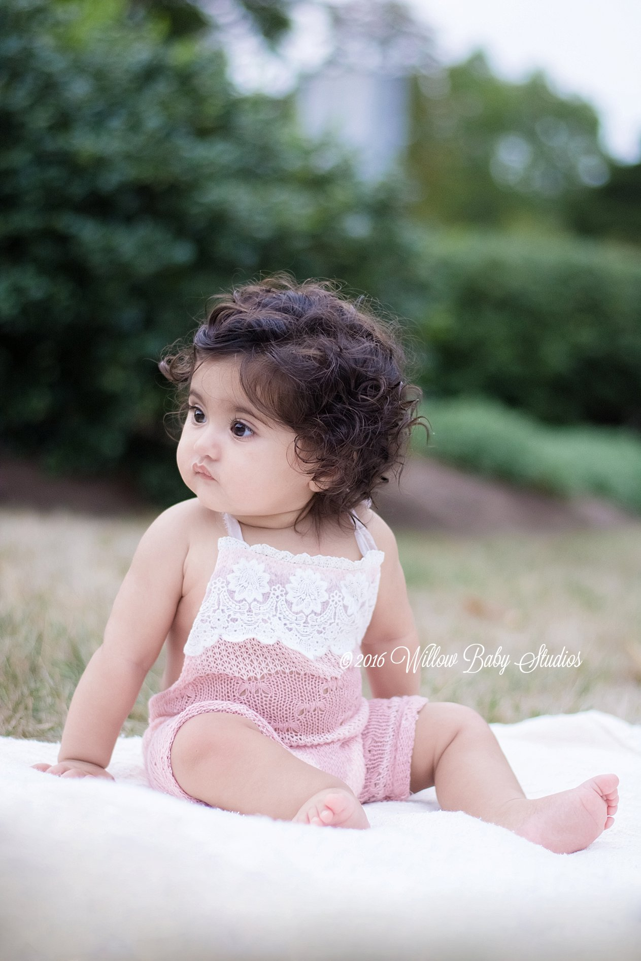 6 month old in pink romper sitting on a blanket in the grass