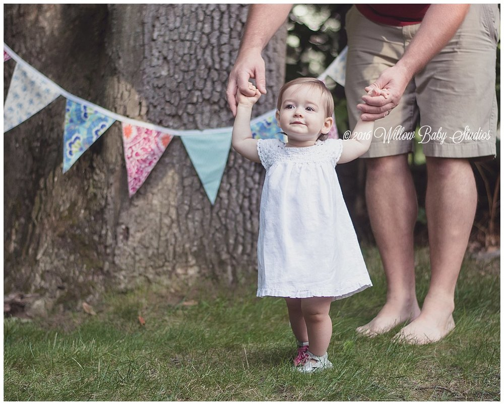 one year old proudly standing and holding her dad's hands