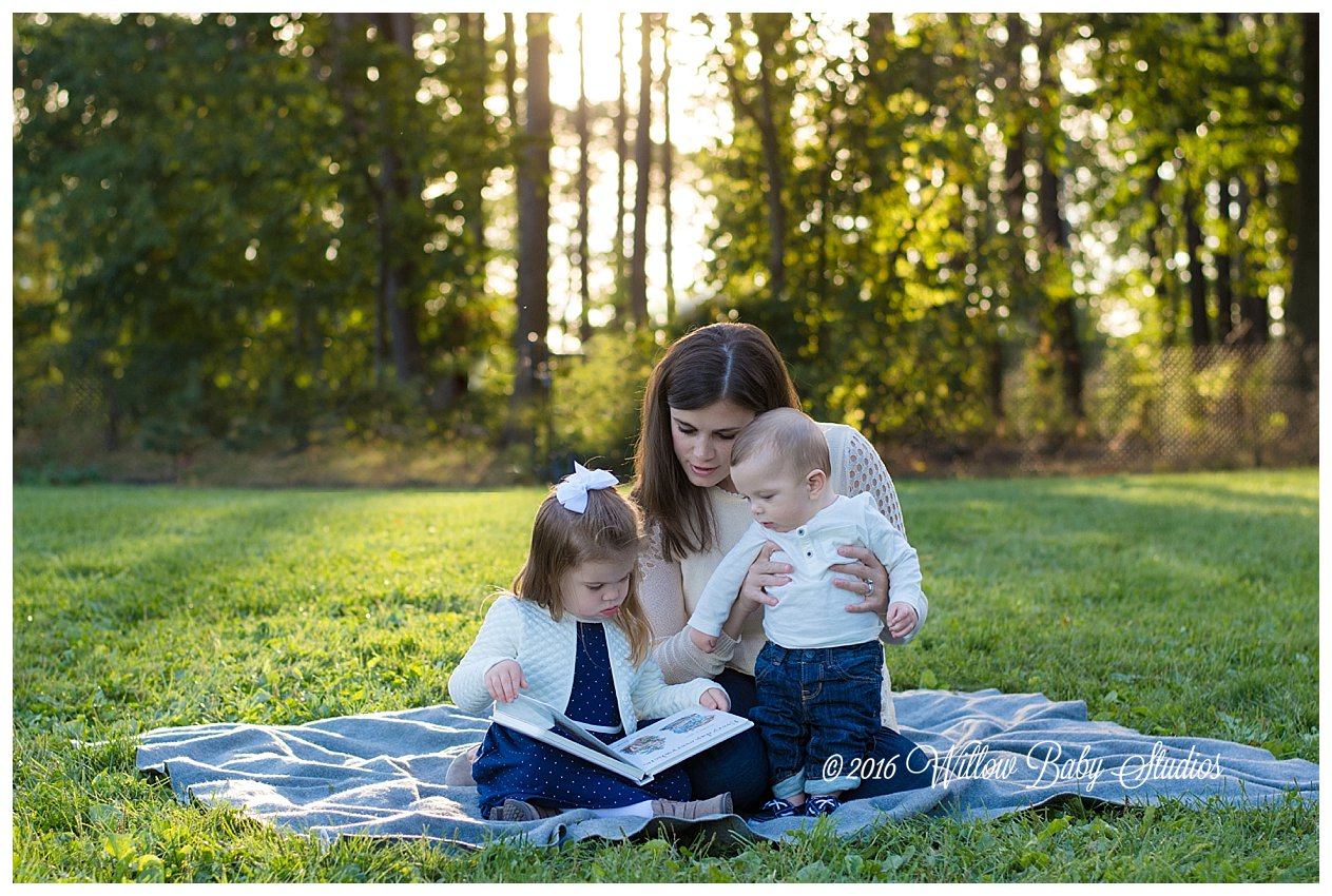 mom reading a book on a blanket with her two young children