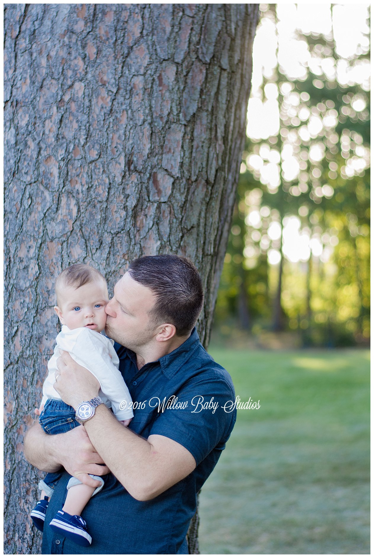 dad kissing his 5 month old son on the cheek on a fall day near fresh pond