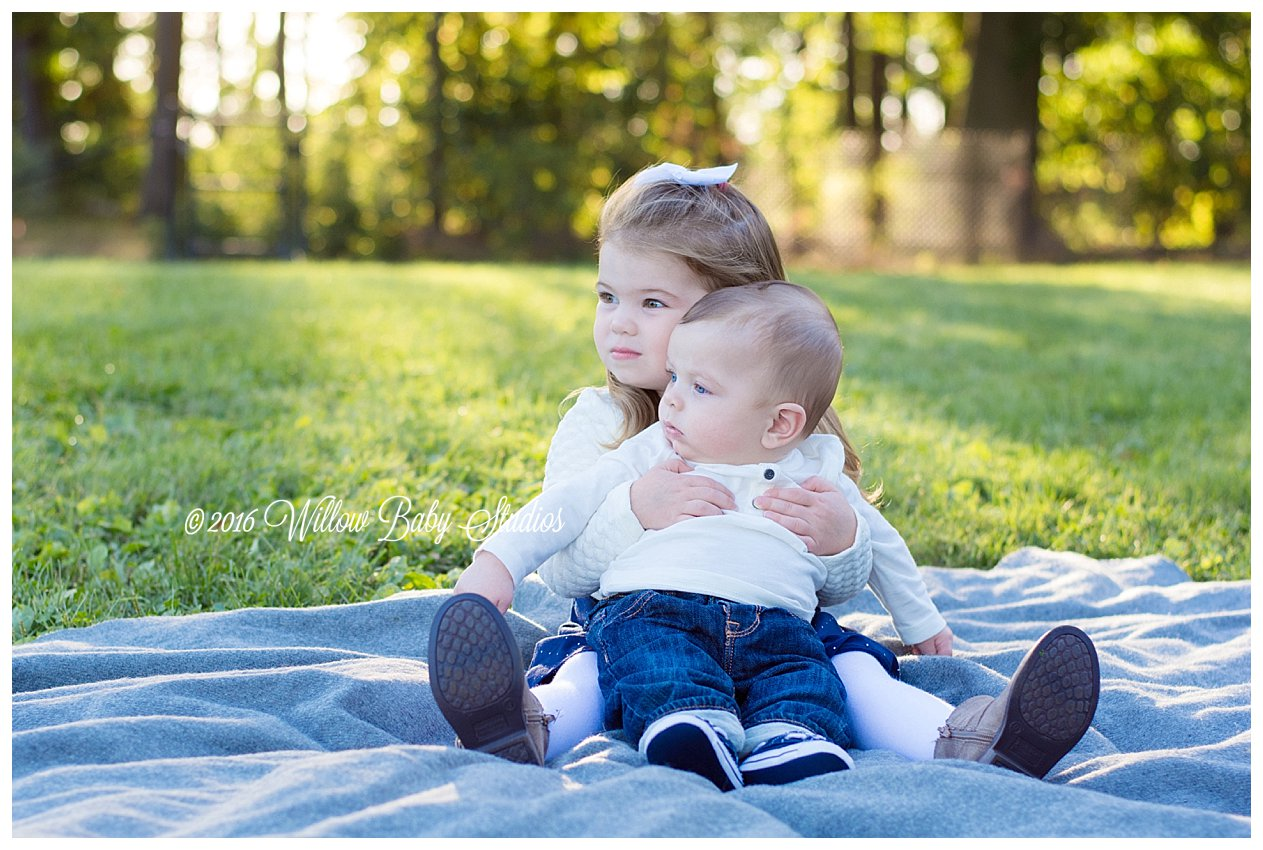 big sister hugging little brother on a fall afternoon