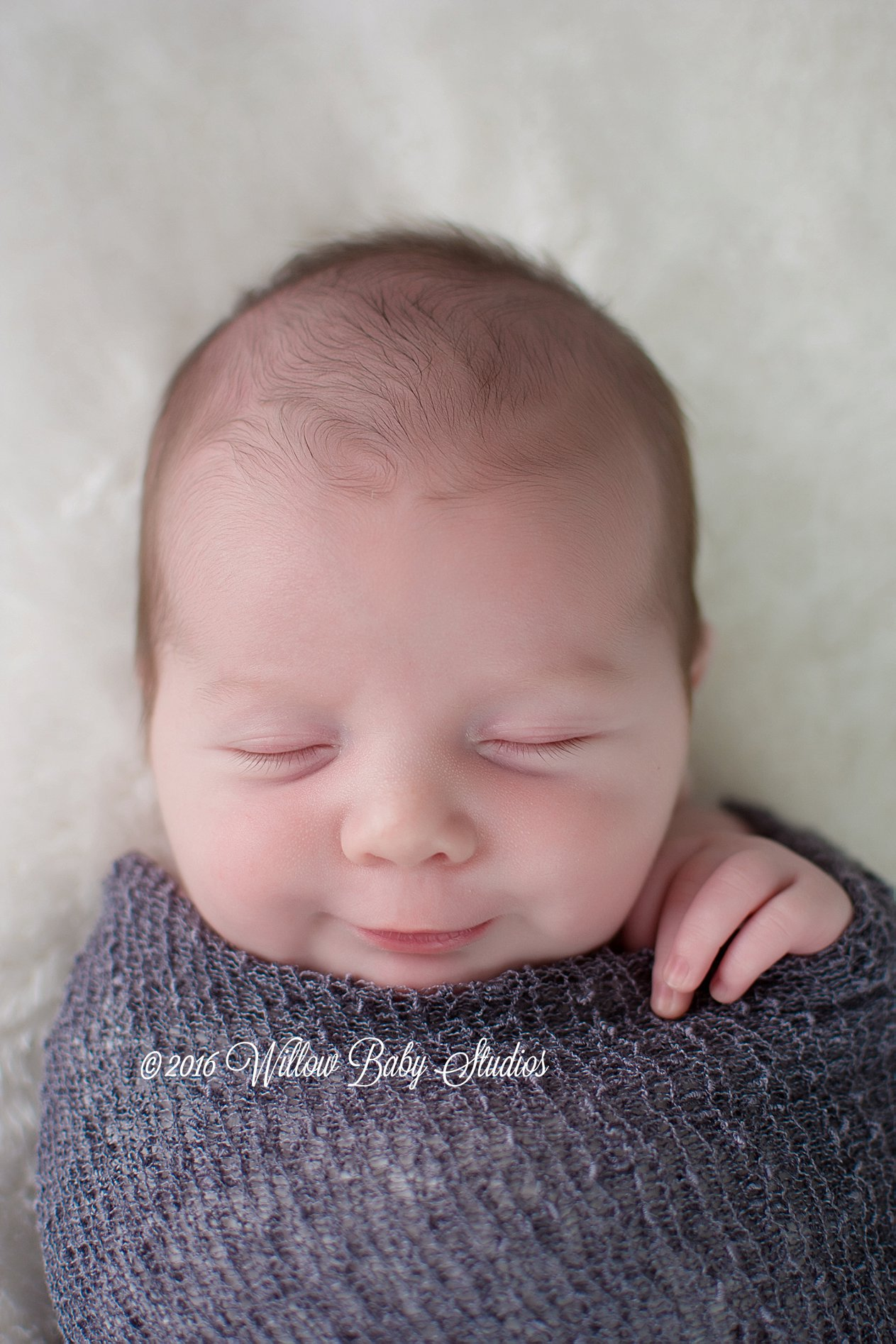 newborn smiling while he sleeps