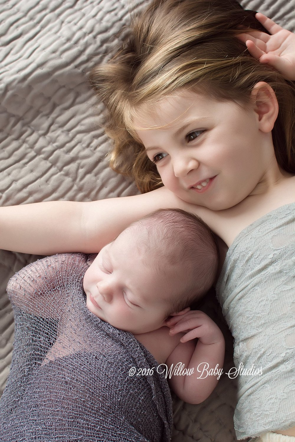 three year old sister snuggling with newborn brother