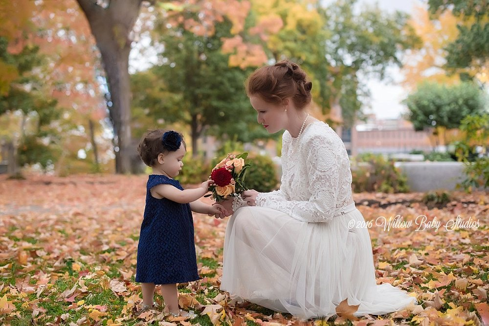 bride and her 1 year old daughter looking at bouquet together