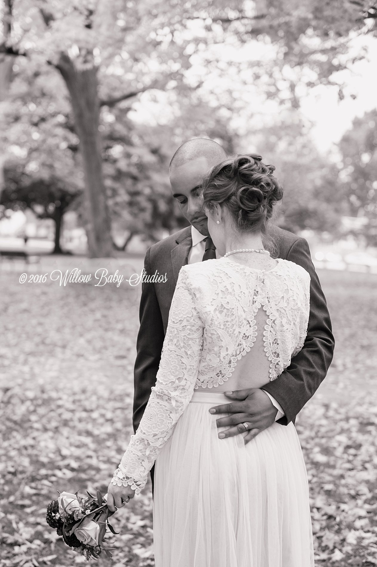 black and white image of married couple embracing outdoors