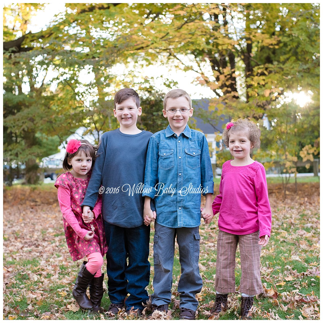 four siblings holding hands outside