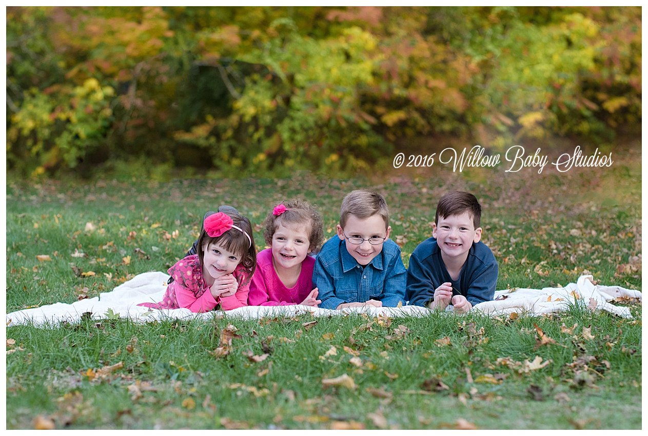 four siblings laying on the grass