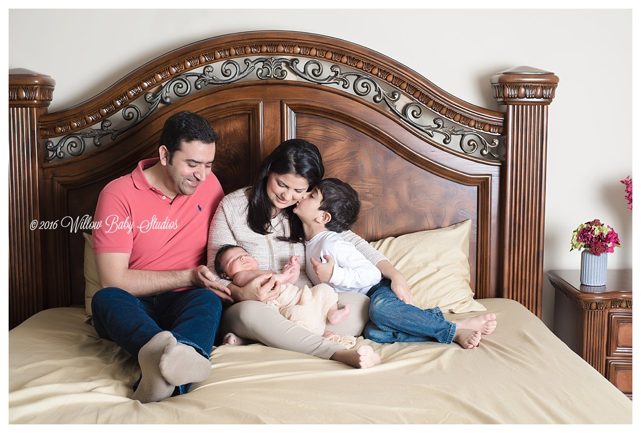 family of four snuggling new baby on the bed