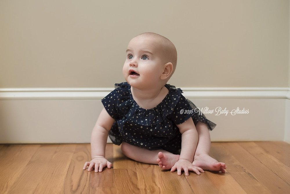 6 month old sitting on the floor looking up sweetly