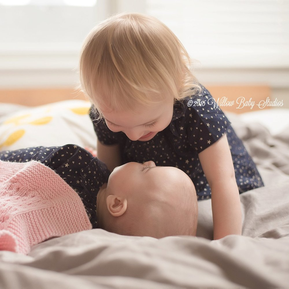 toddler aged girl kissing her 6 month old sister