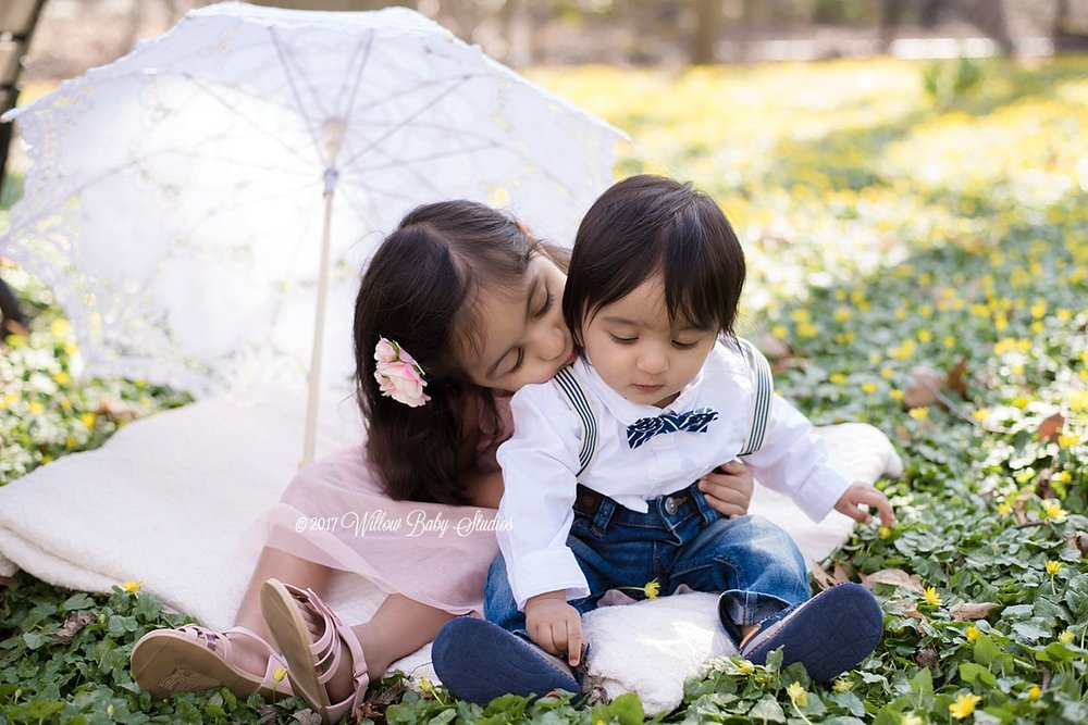 3-year-old-big-sister-snuggling-baby-brother-in-the-grass
