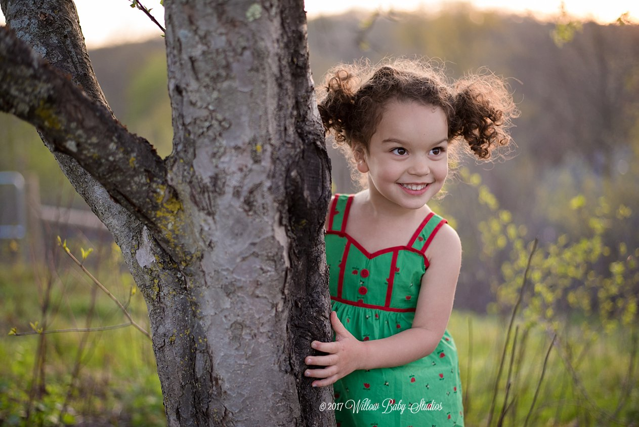 little-girl-grinning-by-tree