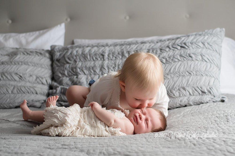 toddler kissing her newborn sister