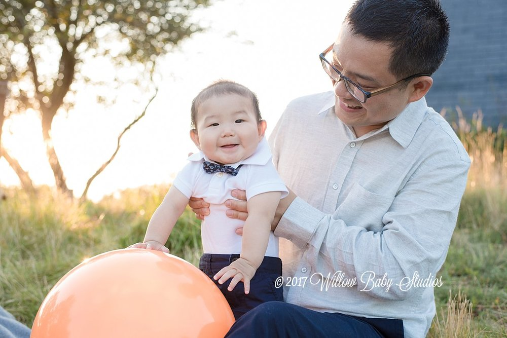 dad with his 6 month old son playing with a big orange ball