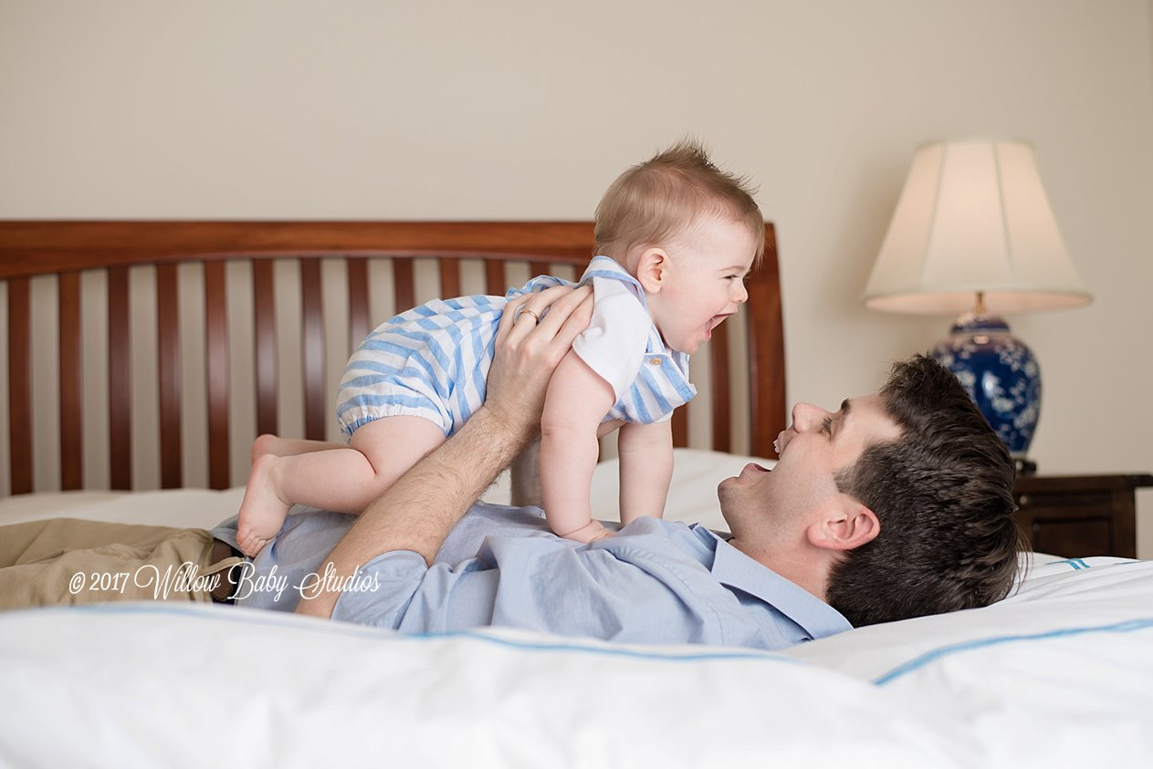 dad laying on bed and holding his baby son in the air