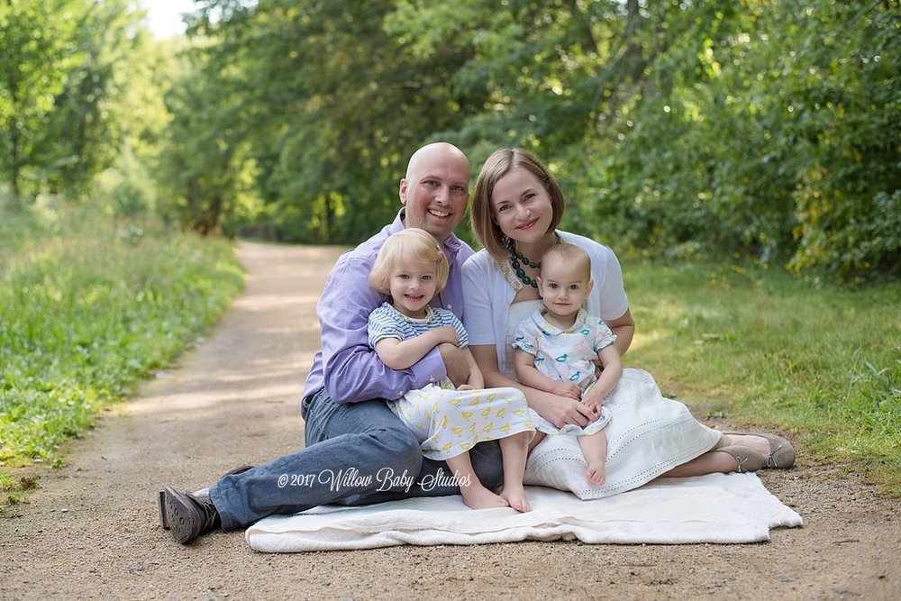 family of four on a pretty outdoor pathway