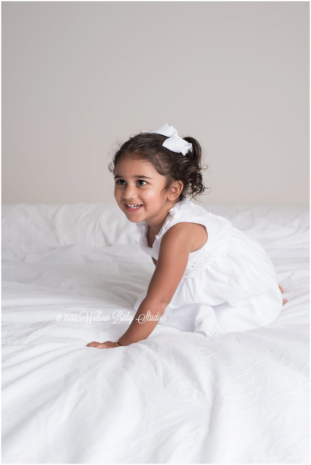 happy toddler playing on the bed