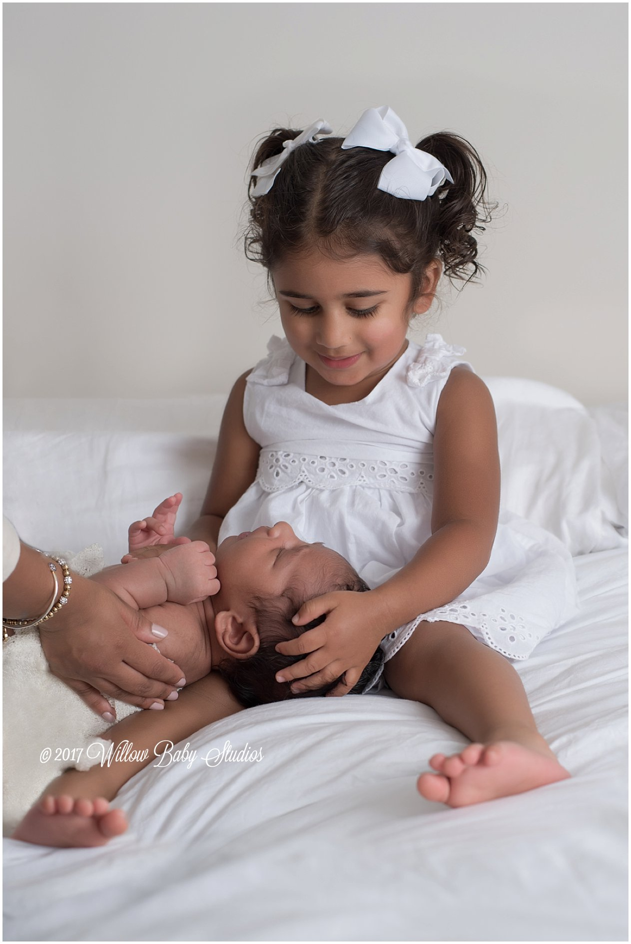 toddler girl holds her new baby brother