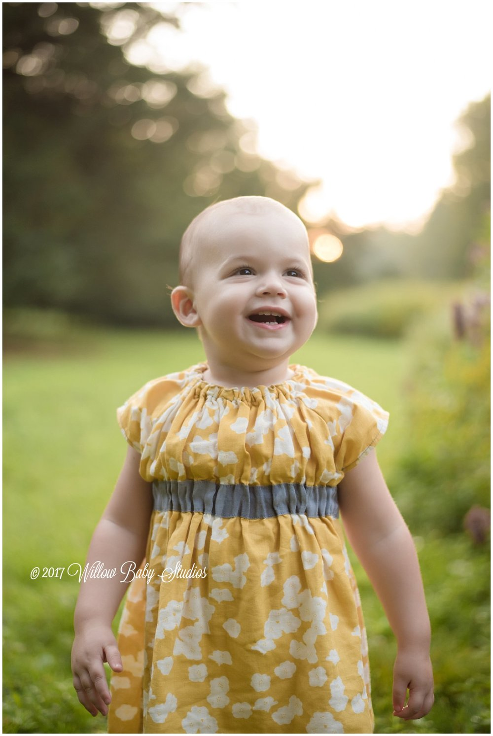 toddler in a yellow dress smiling big on a summer evening