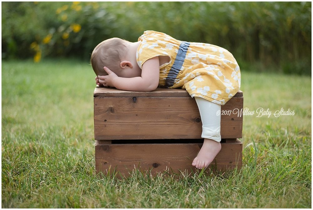toddler peering intently into a wooden box outside
