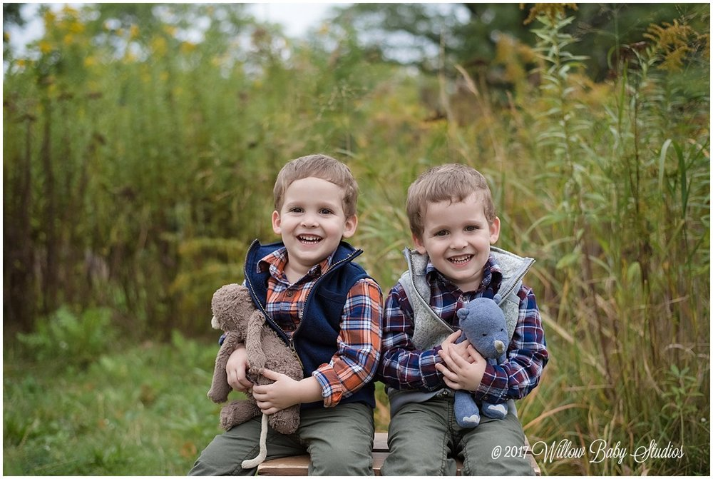 twin three year old boys smiling with their lovies