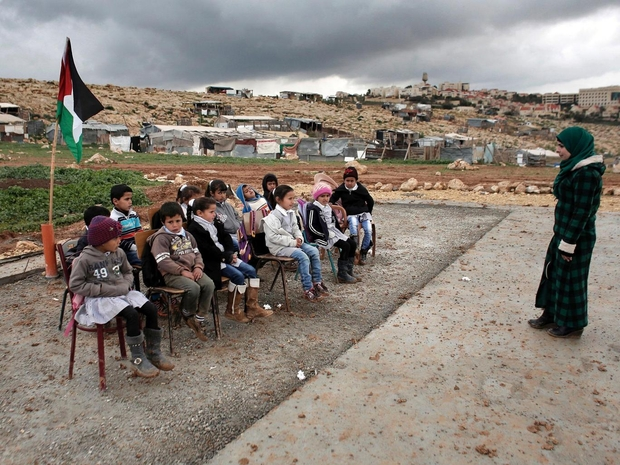 Bedouin children attend school outside in Abu Anwar near the Jewish settlement of Maale Adumim (background), after their classrooms were demolished (AFP)