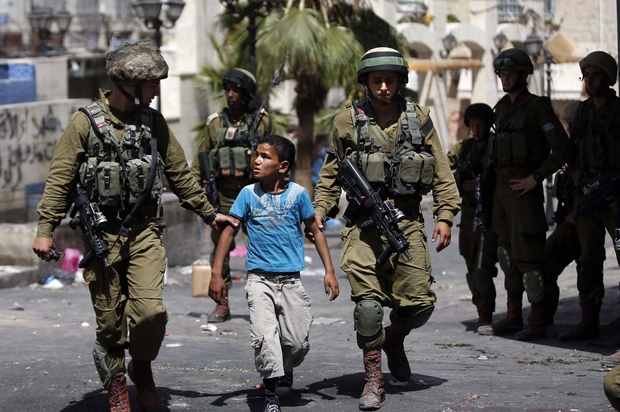 Israeli soldiers arrest a young Palestinian boy following clashes in Hebron in June 2014 (AFP)