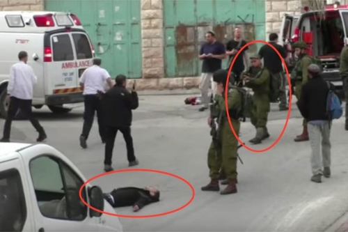 An IDF soldier is seen seconds before shooting a wounded Palestinian man in the head.  (Screenshot/B'Tselem)