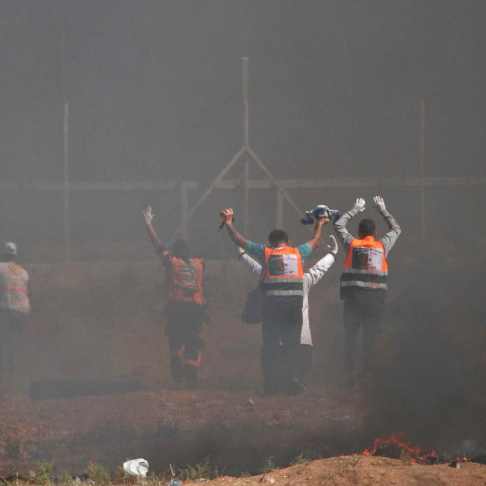Palestinian paramedics raise their arms as they recover injured demonstrators during clashes with Israeli forces near the border between the Gaza Strip and Israel east of Gaza City, May 14, 2018.