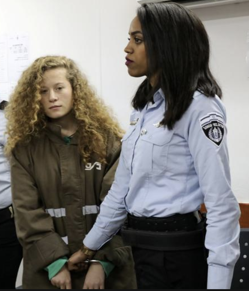 Palestinian teen Ahed Tamimi enters a military courtroom escorted by Israeli Prison Service personnel