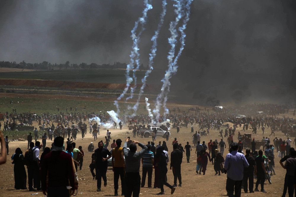 "Palestinian protesters gather to demand the right to return to their homeland, on the occasion of the 70th anniversary of the ""Nakba"", and against U.S. embassy move to Jerusalem at the Israel-Gaza border, in Beit Lahia, in the northern of Gaza Strip, on May 14, 2018. (Photo: Ramez Habboub/APA Images)"