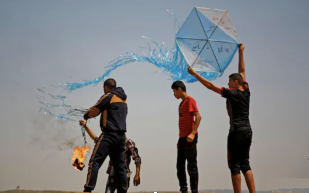 Palestinian protestors prepare to fly a kite loaded with an incendiary during a demonstration along the Gaza-Israel border.