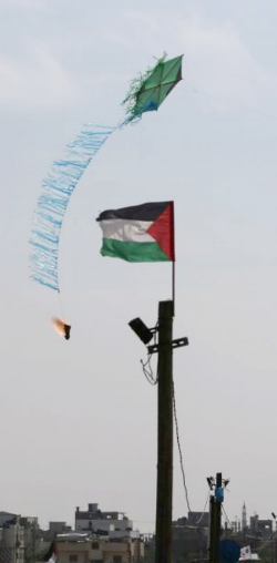 A kite is set on fire by Palestinians, to be sent to the Israeli side during clashes at the Gaza border.