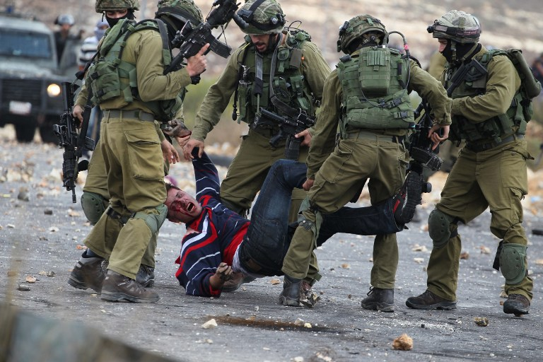 Israeli soldiers detain a Palestinian stone thrower near Beit El