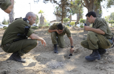 Israeli soldiers inspect a missile launched fro Gaza Strip inside a kibbutz in Israel near the border with Gaza, Wednesday, June 20, 2018.  (AP Photo/Tsafrir Abayov)