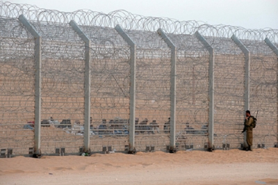 An Israeli soldier checks on African immigrants behind the newly-built fence at the Egypt-Israel border, September 2012.