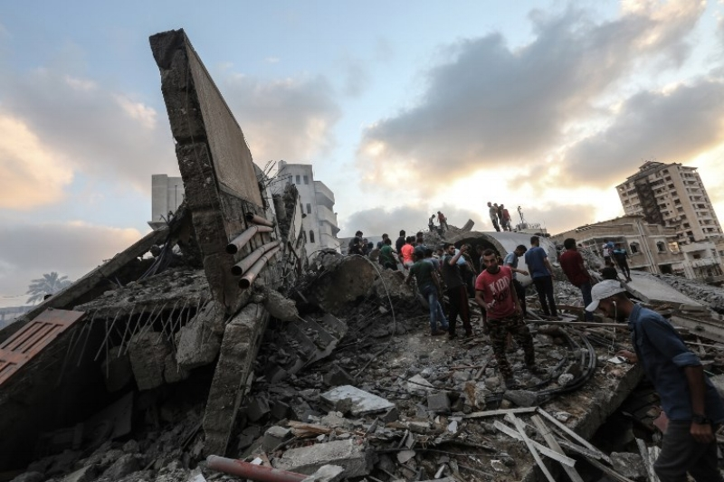 A picture taken on August 9, 2018 shows people inspecting the rubble of a cultural center following an Israeli air strike on Gaza City. (AFP PHOTO / MAHMUD HAMS)
