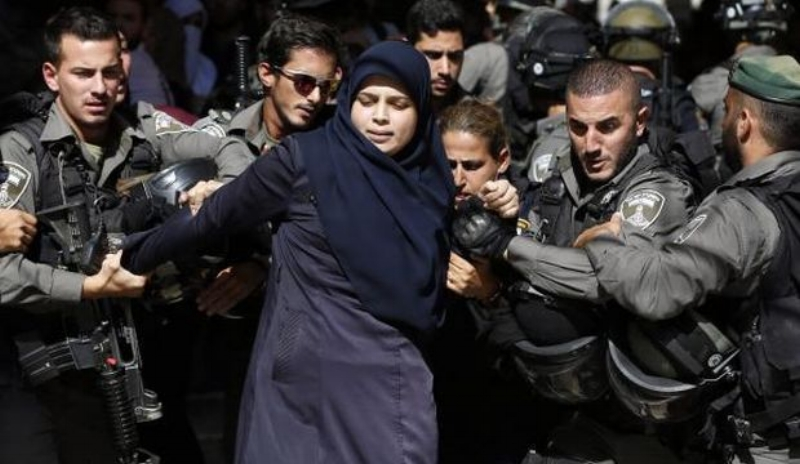 Israeli security forces arrest a Palestinian woman outside Al-Aqsa mosque compound in the old city of Jerusalem, July 26, 2015. (AFP Photo/Ahmad Gharbali)