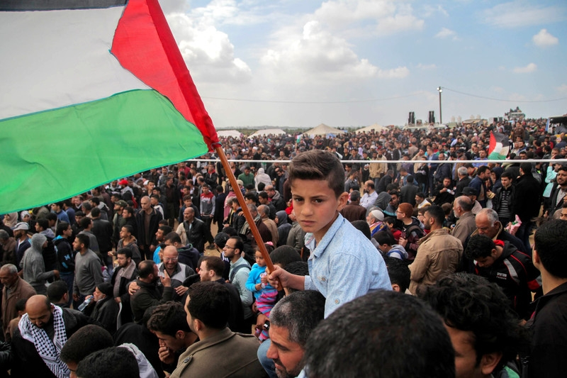 A boy waves a Palestinian flag, among thousands taking part in a Great March of Return rally along Gaza's boundary with Israel, east of Jabaliya, 30 March. Israeli snipers opened fire on protesters all along the boundary, killing 14 that day and injuring 1,400 others. (Ramez Habboub/APA images)
