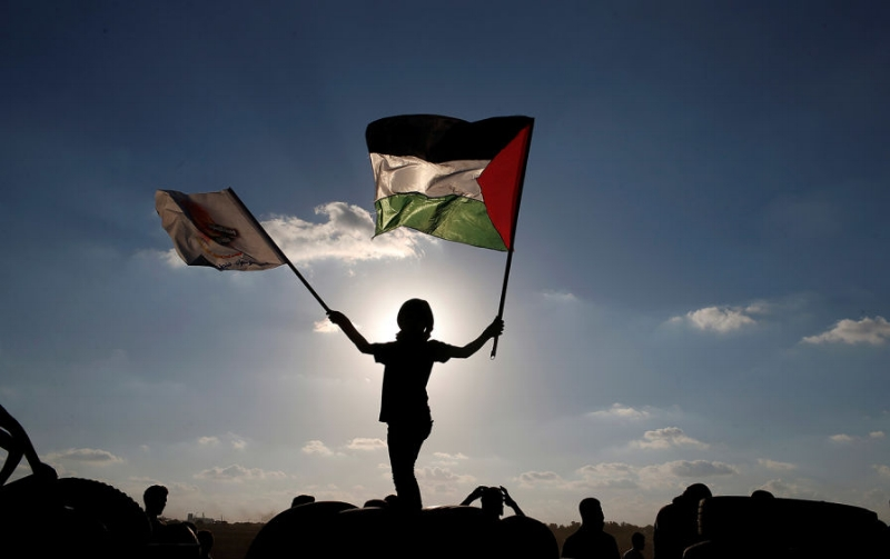 A boy waves a Palestinian flag, at the Israel-Gaza border, during clashes with Israeli troops, at a protest where Palestinians demand the right to return to their homeland, east of Gaza City, April 1, 2018.  (Reuters /Mohammed Salem)