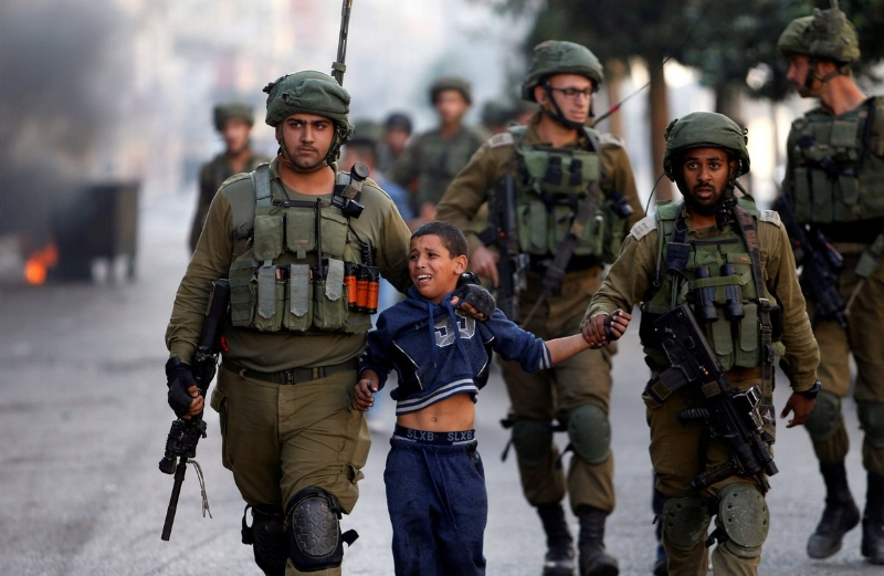 Israeli soldiers detain a Palestinian boy during clashes in West Bank. Credit: Reuters