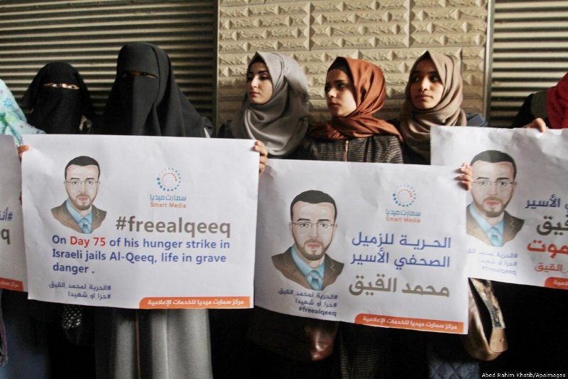 Palestinian journalists hold posters of Palestinian journalist Mohammed al-Qiq who was imprisoned in an Israeli jail during a protest in support of his hunger strike in Rafah in the southern Gaza strip on 7 February 2016 [Abed Rahim Khatib/Apaimages]
