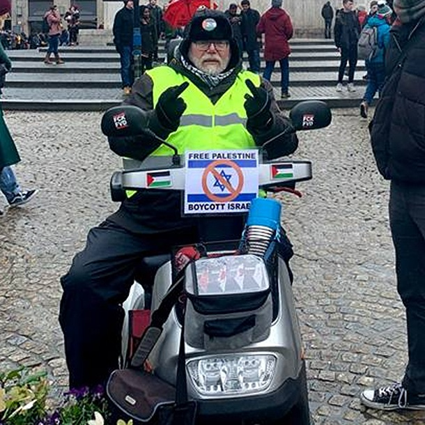Robert-Willem van Norren promoting a boycott of Israel atop an Israel-made mobility scooter in January 2019. (Michael Jacobs)