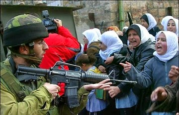 Israeli soldier threatens a group of (unarmed) women.