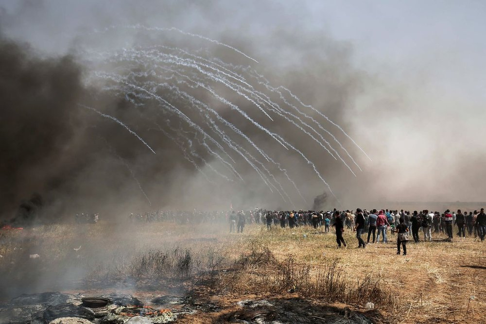 Israeli forces fire tear gas at Palestinian protestors during clashes on the Gaza-Israel border on April 6, 2018. SAID KHATIB/AFP/Getty Images
