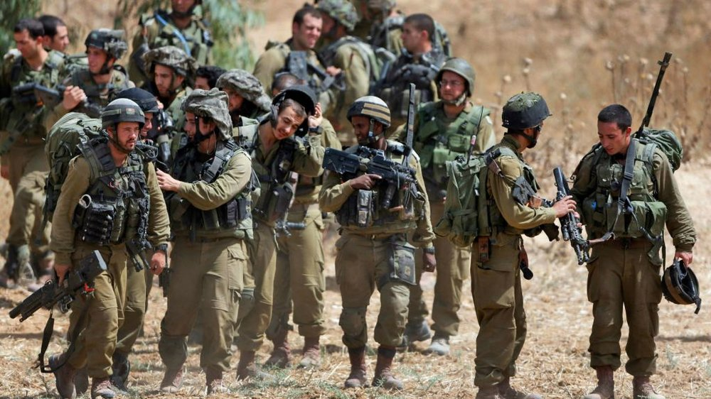 Israeli infantry soldiers get ready to walk to their armored personnel carriers to take up new positions on the Israel-Gaza border, Saturday, July 12, 2014. (AP Photo/Lefteris Pitarakis ( TOI )