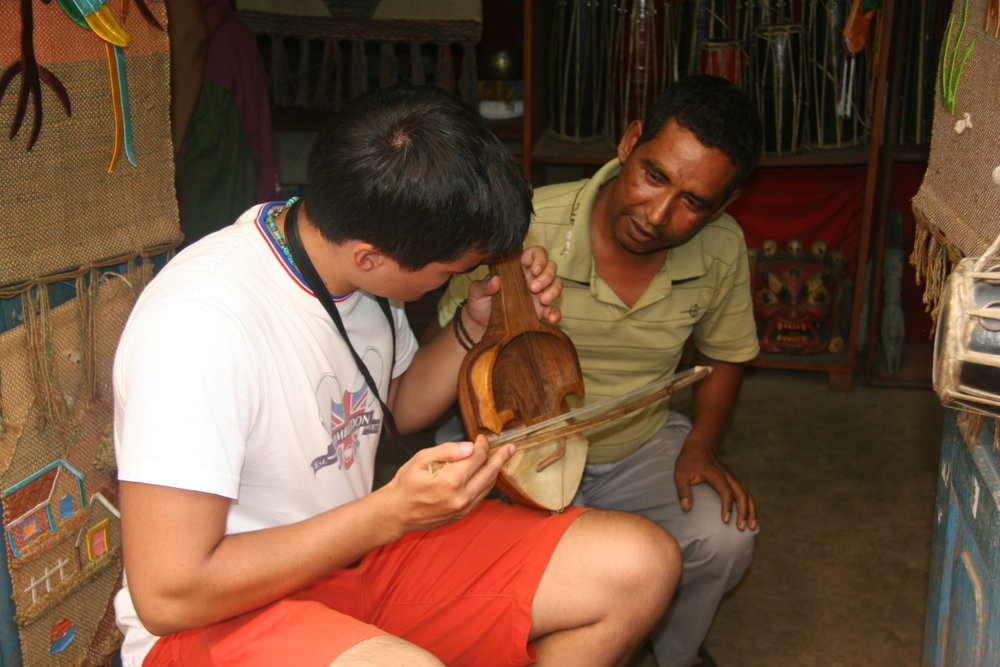 Anthony learning Nepali musical instrument