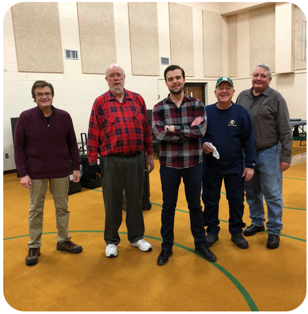 Chris standing with fellow Holt Kiwanis members (including father Tom Trubac, left)serving the community at a Red Cross blood drive.