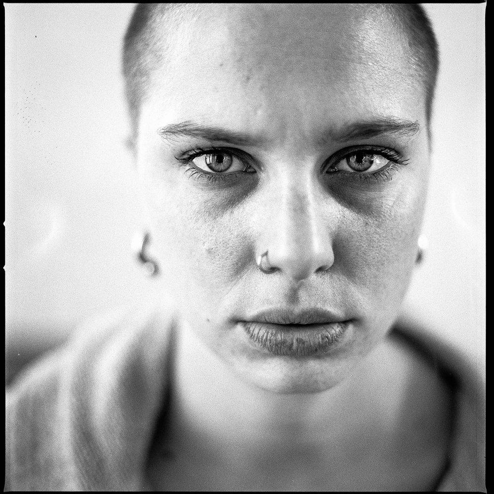 Op deze foto kan je een portret van Charis zien met een lage f-stop. Het topje van haar neus en haar oorringen zijn zeer onscherp, terwijl haar ogen wél de scherpte behouden.  Hasselblad - Tri-X 400 - 70mm